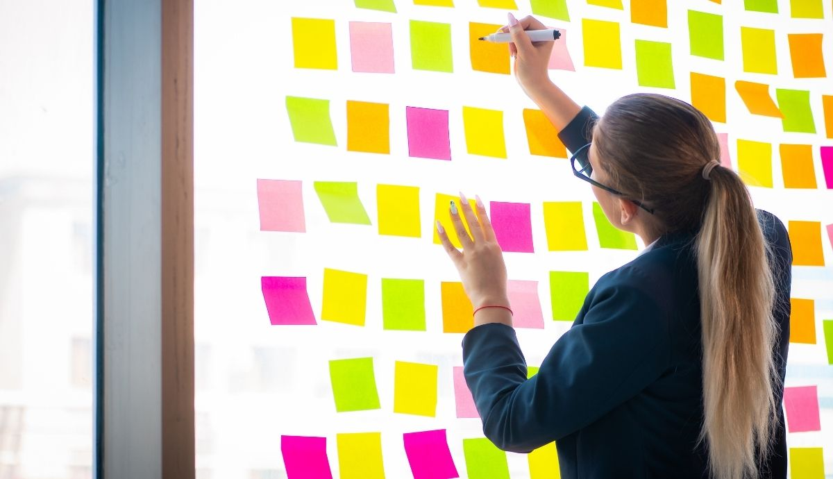 A female knowledge worker in front of a whiteboard with a large number of sticky notes.