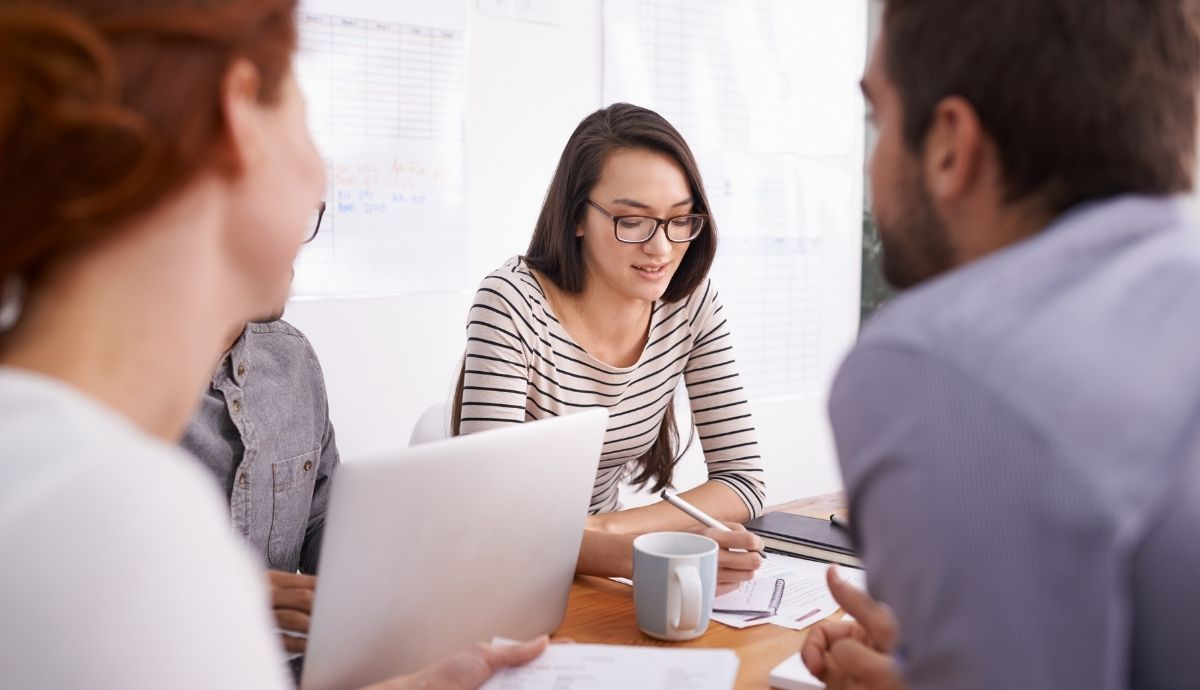 A team in a meeting with a woman taking notes in the center.